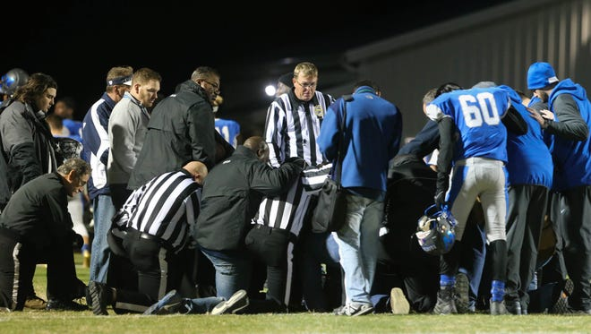Officials, players and coaches gather after a game in which an official collapsed on the field.