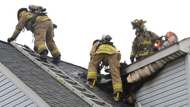 Lancaster Fire Department firefighters work on the roof of a house Monday morning, Dec. 8, 2014, on Kent Court.