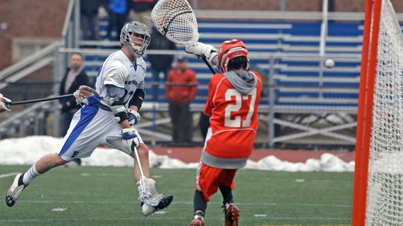 Bronxville's Henry Grass scores on Mamaroneck goalie Jack Dente during Bronxville's 18-7 win at Bronxville High School March 25, 2015. Grass scored seven goals in the season opening lacrosse game.
