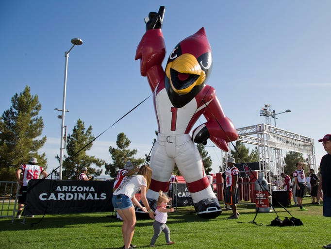 Families gather in front of a giant blow up mascot during Arizona Cardinals Spring Tailgate and Rib Festival at University of Phoenix Stadium in Glendale on Thursday, April 24, 2014.