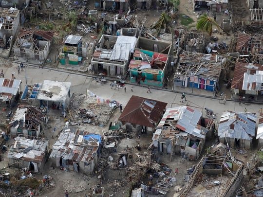 People walk along a street lined with damaged and destroyed