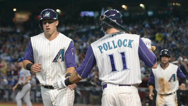 Aug 31, 2017; Phoenix, AZ, USA; Arizona Diamondbacks third baseman Jake Lamb (22) slaps hands with center fielder A.J. Pollock (11) after scoring a run against the Los Angeles Dodgers during the first inning at Chase Field. Mandatory Credit: Joe Camporeale-USA TODAY Sports