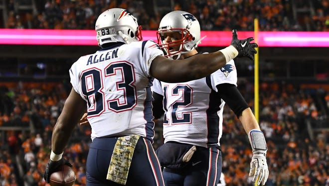 New England Patriots tight end Dwayne Allen (83) celebrates his touchdown reception with quarterback Tom Brady (12) in the second quarter against the Denver Broncos at Sports Authority Field.