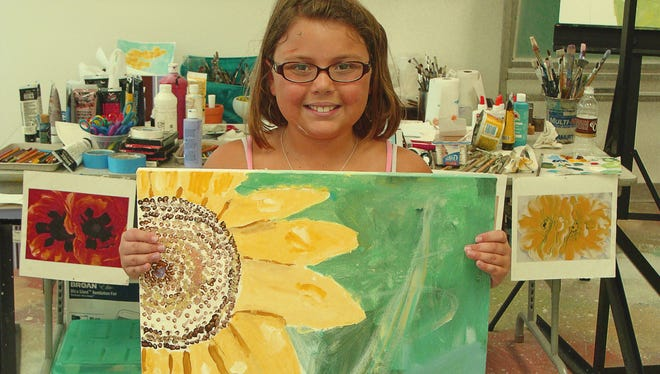 A young artist shows off her creation from a 2017 summer youth art class.