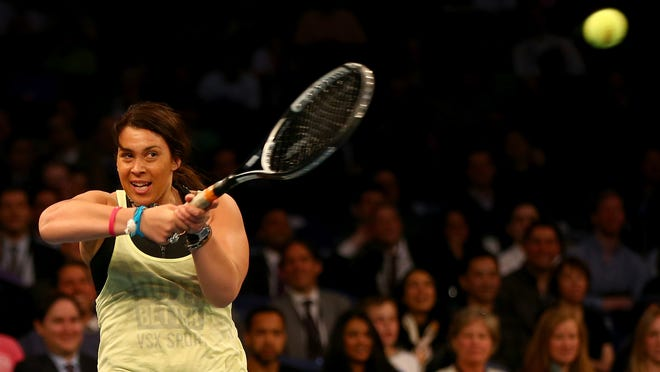 Marion Bartoli of France fills in for Novak Djokovic of Serbia for a point against Andy Murray of Great Britain during the BNP Paribas Showdown at Madison Square Garden.