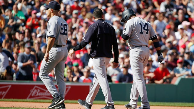 New York Yankees manager Joe Girardi (28) walks off the field with an injured Starlin Castro (14) during the fifth inning of a baseball game against the Boston Red Sox in Boston, Saturday, Sept. 17, 2016.