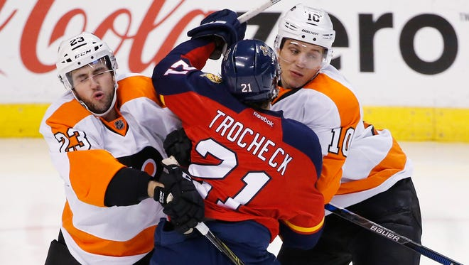 Panthers center Vincent Trocheck (21) is covered by Flyers defender Brandon Manning (23) and center Brayden Schenn.