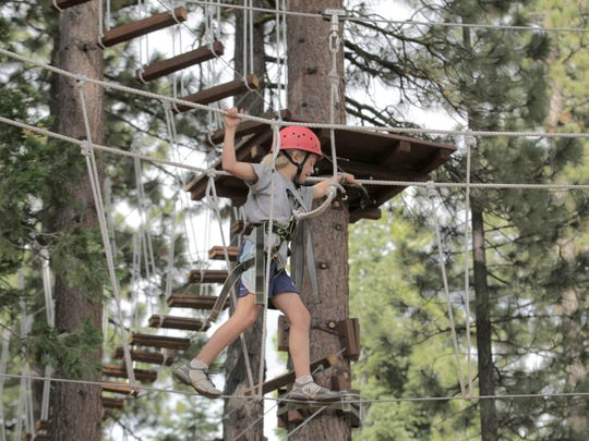 A young climber works her way across one of  the children's courses at Granlibakken's Treetop Adventure Park in Tahoe City Thursday, July 12.