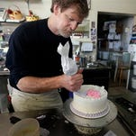 File - In this March 10, 2014 file photo, Masterpiece Cakeshop owner Jack Phillips decorates a cake inside his store, in Lakewood, Colo. Phillips, who refused to make a wedding cake for a gay couple, is to argue Tuesday, July 7, 2015 before the Colorado Court of Appeals that his religious beliefs should protect him from sanctions against his business. (AP Photo/Brennan Linsley, file)