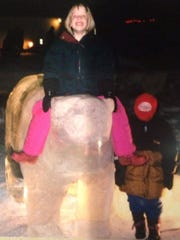 Bobbi Krause and her brother play on a bear carved