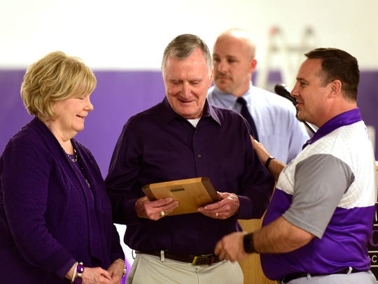 Al Voggenthaler, center, was honored Wednesday as the name was unveiled for Voggenthaler-Dowell Wrestling Complex at Fremont Ross. Ross coach Mike Mezinger hands Voggenthaler a plaque.