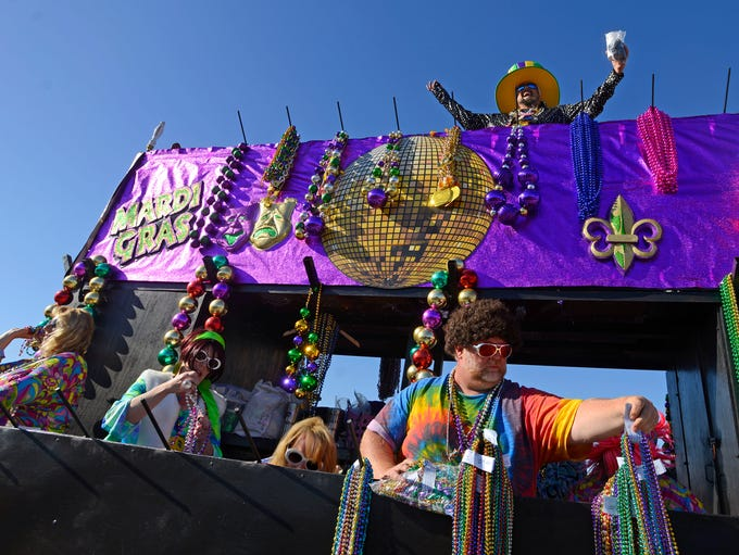 Revelers toss beads Sunday during the Krewe of Wrecks