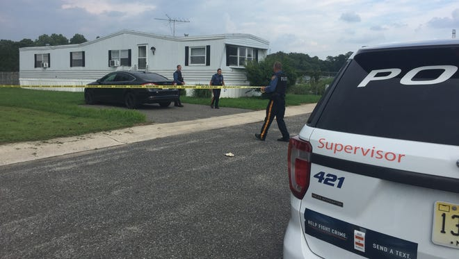 A Vineland officer secures the scene putting police tape around the mobile home where they are investigating a suspicious death on Aug 6.