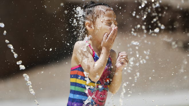 Shaniya (last name withheld by parents) stands in the water at the splash pad to cool down at Desert Breeze Park in Chandler on July 5, 2018.