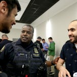Tim Evans, with the Portland Bureau of Police, speaks with Abdulrahman Alanazi, left, 22, and Abdullah Alreshoodi, 25, both of Monmouth, during a criminal justice career fair at the Oregon Public Safety Academy in Salem on Friday, April 29, 2016. Recruiters from city, county, tribal, state and federal agencies were looking for new hires for more than 500 position statewide. Tours were given of the OPSA, including the firearms training facility and the physical abilities test course.