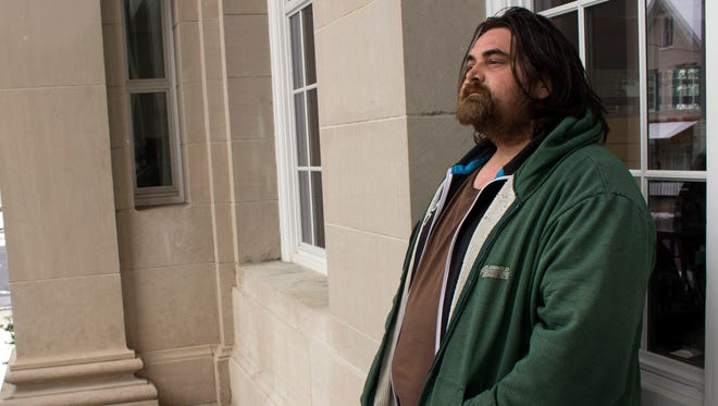 Jason Davies, 34, waits for the Coyle Free Library in Chambersburg to open the morning of Monday, April 2. Davies said he has been chronically homeless most of his adult life, and will often go to the library to use their internet and read some books.