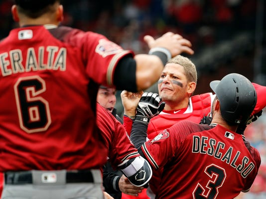 St. Louis Cardinals catcher Yadier Molina, second from right, is held back by Arizona Diamondbacks' Daniel Descalso (3) as Diamondbacks' David Peralta (6) runs into the fray as the benches clear during an altercation in the second inning of a baseball game Sunday, April 8, 2018, in St. Louis. (AP Photo/Jeff Roberson)
