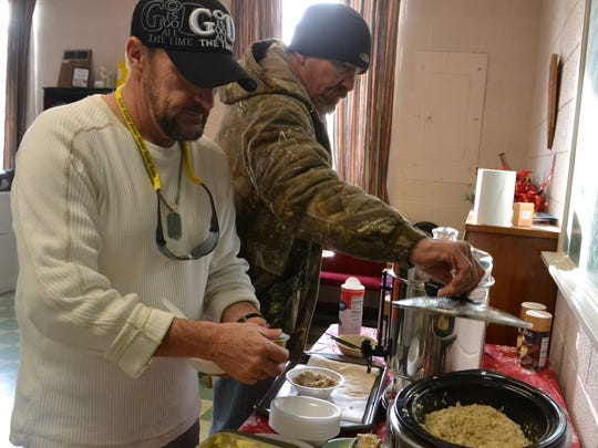 Larry Harbin Jr. of Anderson (left) and Tim Adams gather for lunch at the Anderson Salvation Army shelter Sunday afternoon.