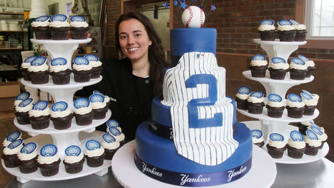 Marisa O'Connor, senior decorator at Homestyle Desserts Bakery in Peekskill, stands with the cupcakes and cake she made for Derek Jeter's number retiring May 13, 2017. Homestyle Desserts Bakery in Peekskill is catering the desserts for the New York Yankees in celebration of Derek Jeter's number retiring.