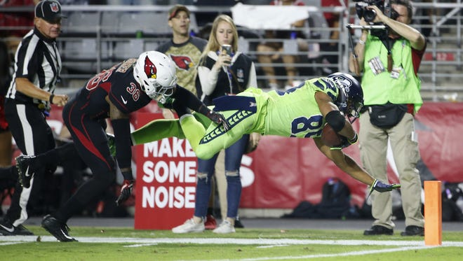Cardinals safety Budda Baker pushes a diving Doug Baldwin out of bounds after a long reception in the fourth quarter on Thursday.