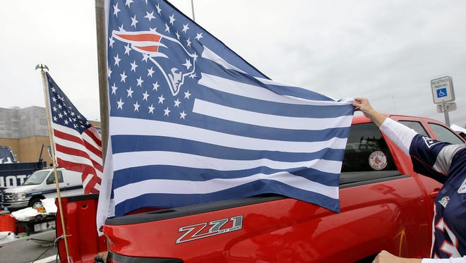 Linda O'Keefe, of Concord, N.H., unfurls a New England Patriots flag while tailgating in the parking lot of Gillette Stadium in Foxborough, Mass.