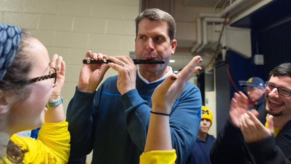 Jim Harbaugh playing piccolo with the U-M band Jan. 24, 2015, at Crisler Center in Ann Arbor.
