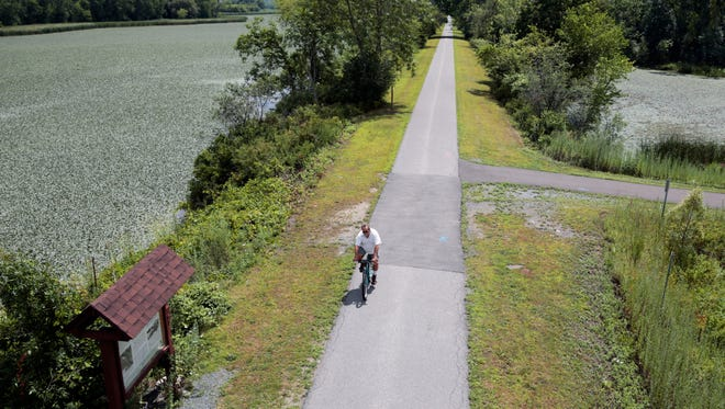 FILE- In this Tuesday, Aug. 4, 2015 file photo, a man bikes along the Canalway Trail in Niskayuna, N.Y. Under a proposal by New York Gov. Andrew Cuomo, the Canalway Trail will become part of a 750-mile paved biking and hiking Empire State Trail scheduled for completion by 2020.