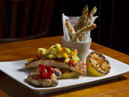 Grilled salmon with pineapple salsa, fingerling potatoes and baked asparagus fries at Front Street Trattoria, which is celebrating 30 years in business. The restaurant's salmon specials change weekly.