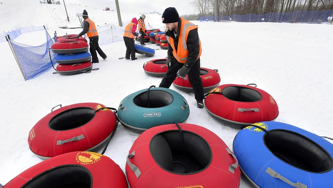 From left: Hawk Island Park workers Travis Coon, Melodie Tillitson, Cynthia Gorton and Joe Stacks haul colorful sledding tubes into place for tube sledding at Hawk Island Park on Jan. 24, 2015.