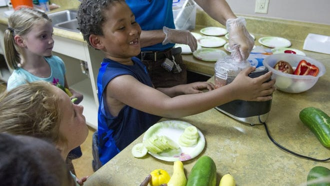 JESSICA TEZAK/NEWS SENTINEL DeModre King, 6, center, presses the button on a food processor to blend vegetables from their garden into fresh salsa in July 2015 during a Grub Club meeting with South Knoxville Elementary at New Harvest Park. The weekly club is sponsored by the Childhood Obesity Coalition whose objective is to teach children about nutritious food. New programs involving Cherokee Health Systems and the University of Tennessee are receiving grants in a similar push to help fight childhood obesity in the Knoxville area.