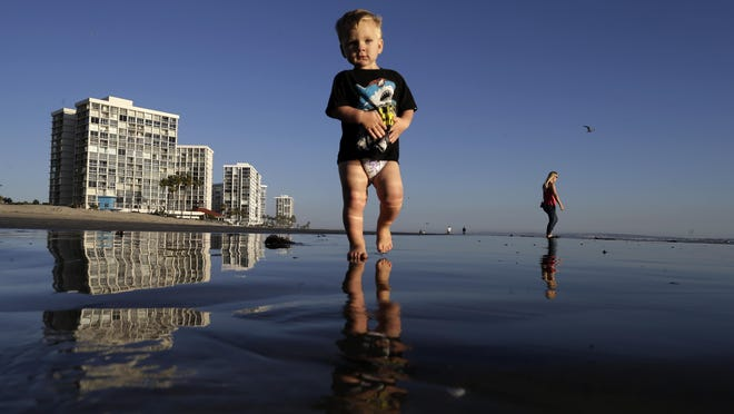Brodie Harsh, center, walks on the beach as his aunt Dusty Sherriffs passes behind him in Coronado, California.