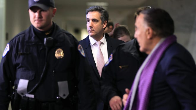 Michael Cohen, President Donald Trump's former lawyer, center, leaves after a closed door Senate Intelligence Committee hearing on Capitol Hill in Washington, Feb. 26, 2019.