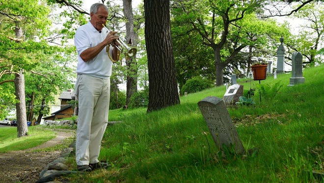 Gary Marquardt plays taps for a deceased veteran at Oak Hill Cemetery in Excelsior, Minn.