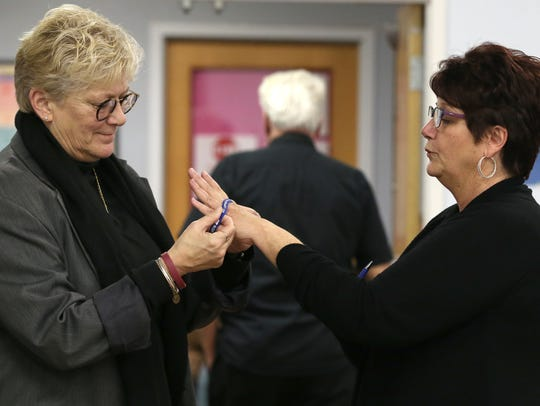 Carol Struble, from Hilton gives Sue Manno of Irondequoit a bracelet with her son's name on it. Struble lost her son to addiction and Manno has a son currently battling addiction. The two connected at Gates to Recovery, a program hosted by the Town of Gates to help addicts and families struggling with the opioid crisis.