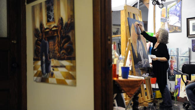 Linda Regula, of Tower Studios, works on a painting a few years ago. She shared the studio with her husband, James Warren. Regula passed away on Saturday at the age of 76.