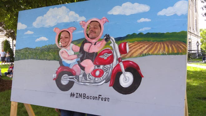"""Jennifer and Jason Grzych pose behind behind an """"Indiana Hogs"""" display Saturday at the Bacon Festival in Delphi."""