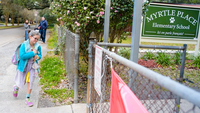 Camille Regard enters the Myrtle Place Elementary campus as her parents, Olivia and Jady Regard, watch from the background. Because the school is located close to their home, the Regards walk their two children to school each day.
