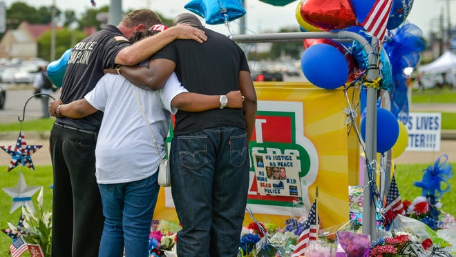 People gather at a memorial in Baton Rouge July 18, 2016 as they remember  the three Baton Rouge police officer who were ambushed and killed.
