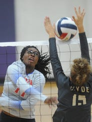 Cooper's Daniece Edwards, left, hits the ball over