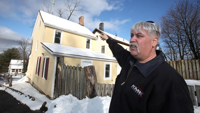 Firefighter Ken Patterson stands outside a Haverstraw house where he fought a stubborn fire in 2011. He got lost inside the burning home and passed out from smoke inhalation; the house had been illegally subdivided into apartments.