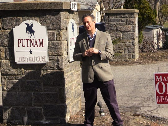 David Mckay Wilson, investigative reporter for lohud, stands next to a campaign sign for Putnam County Executive MaryEllen O'Dell at the Putnam County Golf Course in Mahopac on April 11, 2018.