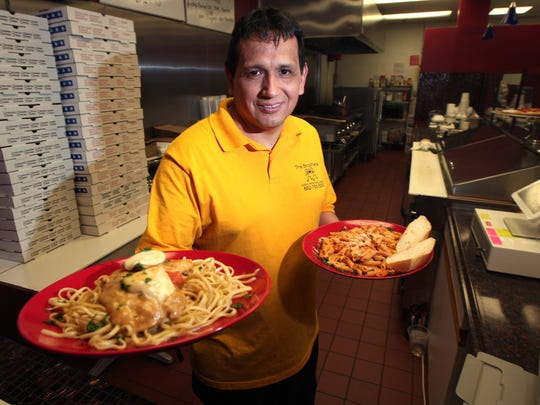 Owner Homero Ortiz with Chicken Milano and Penne Vodka dishes at his new Brothers Italian-American Cuisine. March 26, 2015. East Hanover, N.J.
