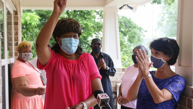 Brenda Montgomery waves the key to her new home at the Habitat for Humanity dedication ceremony on Friday. Montgomery's home was the first Habitat for Humanity home dedicated in Tuscaloosa since the start of the COVID-19 pandemic.