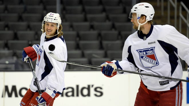 Rangers left wing Carl Hagelin, left, watches as defenseman Anton Stralman juggles a puck on his stick during practice Friday at Staples Center in Los Angeles.