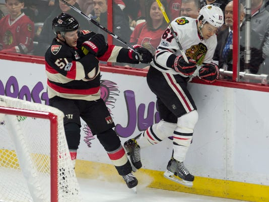 Ottawa Senators center Tommy Wingels sends Chicago Blackhawks center Tanner Kero into the boards during the first period of an NHL hockey game, Thursday, March 16, 2017 in Ottawa, Ontario. (Adrian Wyld/The Canadian Press via AP)
