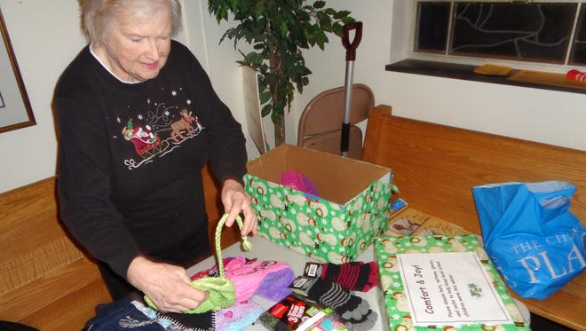 Ginny Mouillesseaux sorts through donations of hats, gloves and other clothing items at Our Lady of Good Counsel Church in Endicott. Parishioners buy or make the items, and Mouillesseeaux donates them to local schools as part of the Joy Box program.