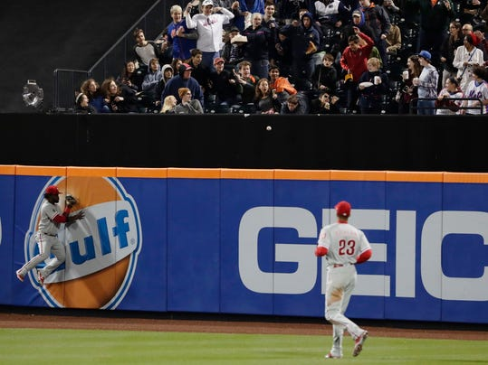 Philadelphia Phillies' Odubel Herrera, left, and Aaron Altherr (23) chase a ball hit by New York Mets' Neil Walker for a three-run home run during the third inning of a baseball game Thursday, April 20, 2017, in New York. (AP Photo/Frank Franklin II)