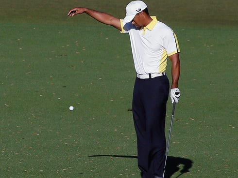 In this file photo, Tiger Woods takes a drop on the 15th hole after his ball went into the water during the second round of the 2013 Masters golf tournament, but later accepted a two-stroke penalty after the drop was determined to be improper. Woods