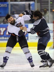 Knoxville Icebears' Dennis Sicard (left) and Ice Flyers' Joe Bueltel fight at center ice Sunday at the Pensacola Bay Center.