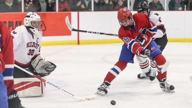Natick's Will Genaske flips the puck into the net during the Bay State Conference hockey game against Wellesley at the Boston Sports Institute in Wellesley on Jan. 18.